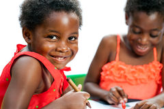 Hållande färgpenna för gullig afrikansk unge med vännen i bakgrund Royaltyfri Fotografi