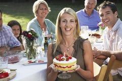 Hållande födelsedagkaka för kvinna med familjen i trädgård Arkivfoto