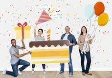 Hållande födelsedagkaka för lyckligt olikt folk arkivbilder