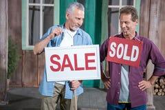 Hållande försäljningstecken för hög man, medan ett annat maninnehav sålde allsång Royaltyfria Bilder