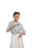 Hållande förstoringsglas för attraktiv afrikansk amerikankvinna som isoleras på vit Royaltyfri Foto