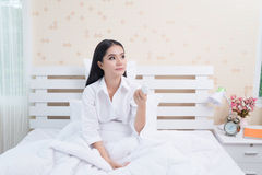 Hållande fjärrkontroll för ung kvinna av luftkonditioneringsapparaten som isoleras på vit bakgrund fotografering för bildbyråer