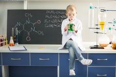 Hållande flaska för skolflicka med den kemiska prövkopian, medan sitta Royaltyfria Bilder