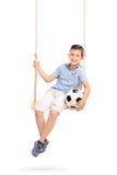 Hållande fotboll för avkopplad pojke som placeras på en gunga Royaltyfri Bild