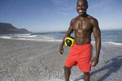 Hållande fotboll för man på stranden Royaltyfria Bilder