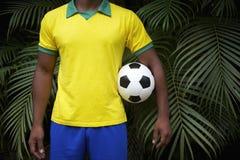 Hållande fotbollboll för brasiliansk fotbollsspelare i djungel royaltyfria foton