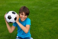 Hållande fotbollboll för pojke Royaltyfri Bild