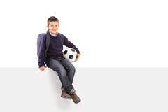 Hållande fotbollboll för skolpojke som placeras på en panel Arkivfoton