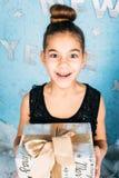 Hållande gåva för förvånad flicka och se på kamera över blå bakgrund Arkivfoton