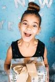 Hållande gåva för förvånad flicka och se på kamera över blå bakgrund Royaltyfri Foto