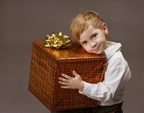 Hållande gåvaask för barn. Pojke med gåva arkivbilder