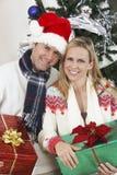 Hållande gåvor för par i Front Of Christmas Tree royaltyfria foton