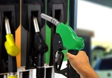 Hållande gasdysa på bensinstationen Arkivbild