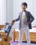 Hållande gitarr för tonårs- asiatisk pojke som poserar & ler i sovrum Royaltyfri Fotografi