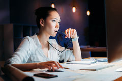 Hållande glasögon för eftertänksam asiatisk affärskvinna och se datorbildskärmen Arkivfoton