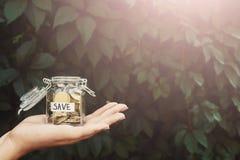 Hållande glass krus för hand med mynt med RÄDDNINGetiketten royaltyfria bilder