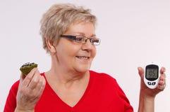 Hållande glucometer för lycklig hög kvinna och ny muffin som mäter och kontrollerar sockernivån, begrepp av sockersjuka Royaltyfri Fotografi
