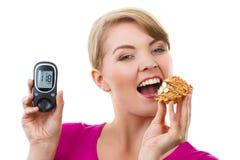 Hållande glucometer för lycklig kvinna och äta den nya muffin som mäter sockernivån, begrepp av sockersjuka Royaltyfri Foto