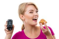 Hållande glucometer för lycklig kvinna och äta den nya muffin som mäter sockernivån, begrepp av sockersjuka Royaltyfria Foton