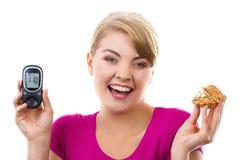 Hållande glucometer för lycklig kvinna och ny muffin som mäter och kontrollerar sockernivån, begrepp av sockersjuka Royaltyfria Foton
