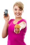 Hållande glucometer för lycklig kvinna och ny muffin som mäter och kontrollerar sockernivån, begrepp av sockersjuka Royaltyfri Foto