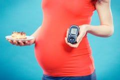Hållande glukosmeter för gravid kvinna med den bra resultatsockernivån och stycket av ostkaka, sockersjuka och näring under havan arkivbild