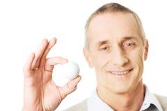 Hållande golfboll för mogen man Royaltyfri Bild