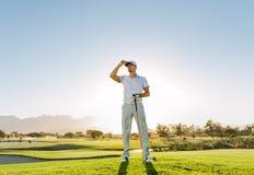 Hållande golfklubb för manlig golfare på fält Arkivfoton