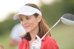 Hållande golfklubb för ståendekvinna royaltyfria bilder