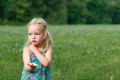 Hållande gräshoppa för förtjusande ung flicka Arkivbild