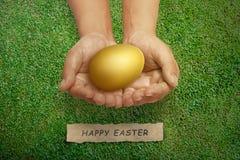 Hållande guld- easter för folkhand ägg med den lyckliga easter hälsningen Arkivfoto