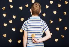 Hållande guld- hjärta för pojke bak hans baksida Royaltyfri Foto