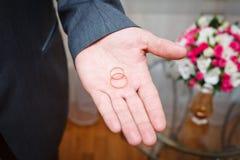 Hållande guld- vigselringar för brudgum på gömma i handflatan Royaltyfria Bilder