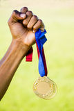 Hållande guldmedalj för idrottsman nenhand efter seger Arkivbild