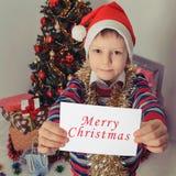 Hållande hälsningkort för pojke christmastime Arkivfoton