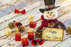 Hållande hälsningkort för snögubbe för nytt år eller jul med julprydnader royaltyfria foton