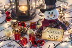 Hållande hälsningkort för snögubbe för nytt år eller jul med julprydnader arkivfoton