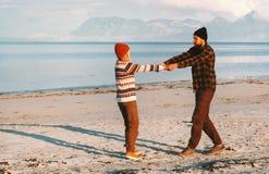 Hållande händer för lyckliga par som går på strandman och den unga familjen för kvinna royaltyfri fotografi