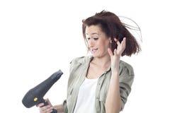 Hållande hårtork för förskräckt kvinna Arkivbild