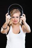 Hållande hörlurar för härlig flicka på svart arkivfoton