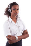 Hållande hörlurar med mikrofon för afrikansk amerikanhelpdeskarbetare - svarta människor Arkivfoto