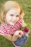 Hållande hallon för flicka i henne hand Arkivfoto