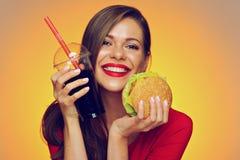 Hållande hamburgare för lycklig kvinna med colaexponeringsglas Arkivbilder