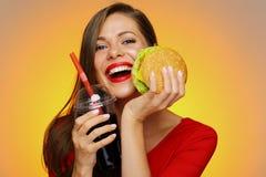 Hållande hamburgare för lycklig kvinna med colaexponeringsglas Royaltyfri Fotografi