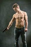 Hållande handeldvapen för idrotts- topless man arkivfoton