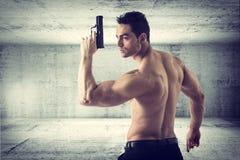 Hållande handeldvapen för idrotts- topless man i konkreta Hall royaltyfri bild