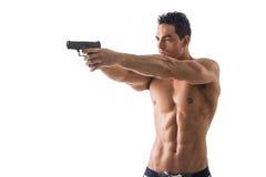Hållande handeldvapen för idrotts- topless man mot vit royaltyfri bild