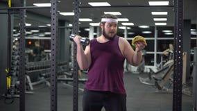 Hållande hantel för sjukligt fet man som äter hamburgaren som vägrar från att göra sporten, böjelse stock video