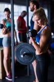 Hållande hantlar för ung kvinna i idrottshall Arkivbild