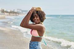 Hållande hatt för nätt afro amerikansk flicka på head le Royaltyfria Bilder